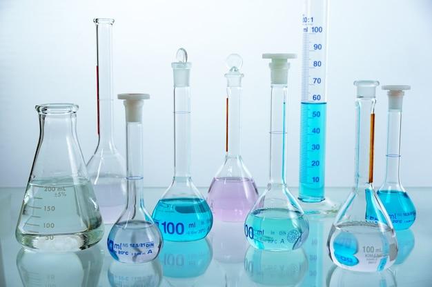 Set di bicchieri di vetreria da laboratorio riempiti di liquido di colore diverso.