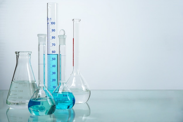 Set di bicchieri di vetreria da laboratorio riempiti di liquido di colore diverso. Foto Premium