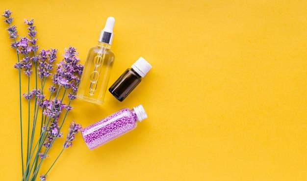 Impostare prodotti cosmetici per la cura della pelle alla lavanda prodotti di bellezza naturali termali erbe fresche di fiori di lavanda su sfondo giallo olio essenziale di lavanda siero crema perline da bagno piatto spazio copia laici