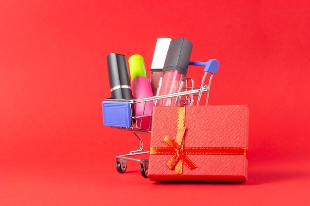 Un set di cosmetici per rossetto e lucidalabbra, polvere, ombretto e un carrello della spesa su uno sfondo rosso brillante. il concetto di acquisto di cosmetici, shopping online, vacanze
