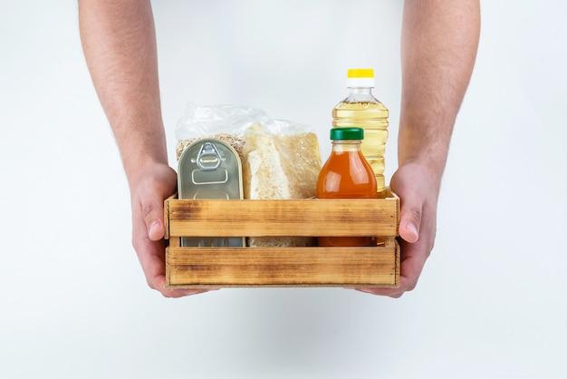 Un set di prodotti per la conservazione a lungo termine e le mani degli uomini su un muro bianco. donazioni di cibo o concetto di consegna di cibo