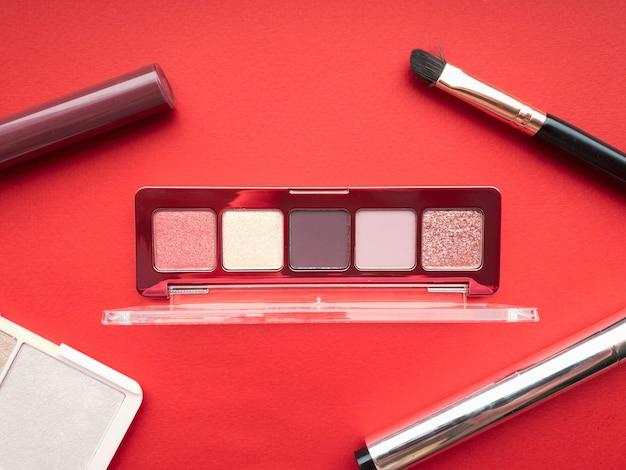 Un set di prodotti per il trucco tra cui ombretto, lucidalabbra, mascara, pennello per il trucco e evidenziatore su sfondo rosso. concetto di bellezza.