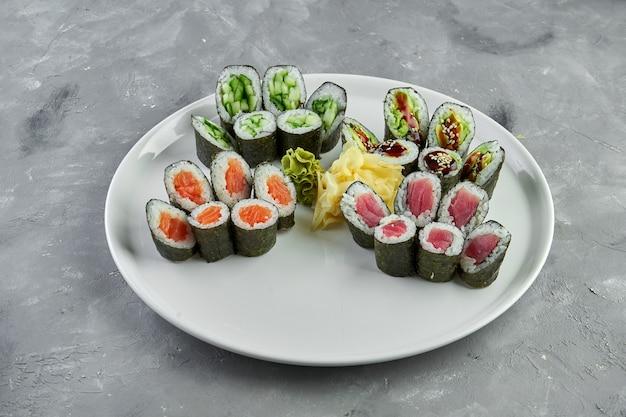 Set di involtini di sushi maki con salmone, tonno, avocado e cetriolo in un piatto bianco su grigio