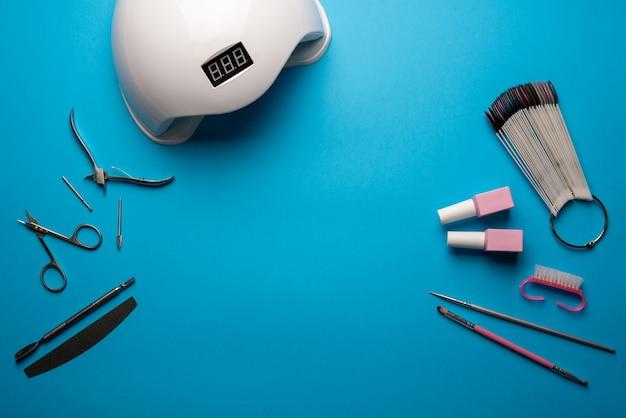 Set di strumenti per manicure e accessori su sfondo blu