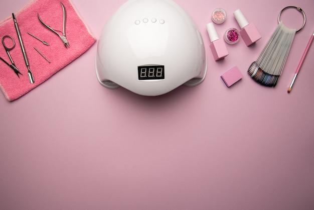 Set di strumenti per manicure e accessori su uno sfondo rosa