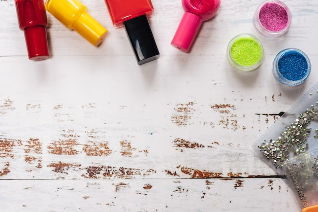 Set di strumenti per manicure e smalti per unghie su un fondo di legno bianco.
