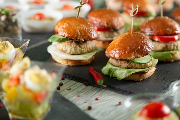 Set di hamburger di carne a bordo nero sul tavolo di legno