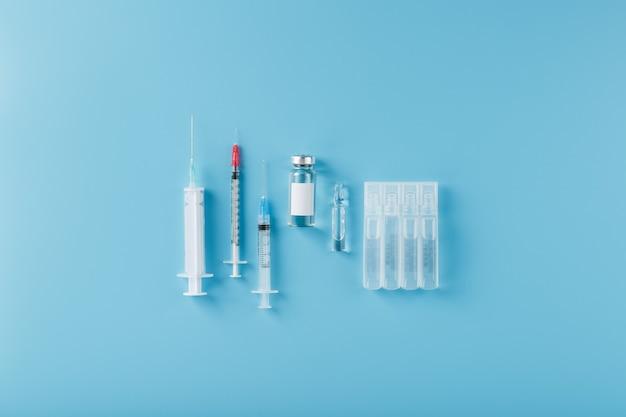 Un set di medicinali in fiale e siringhe per il trattamento di virus, vaccinazioni e malattie. su sfondo blu, spazio libero, vista dall'alto.