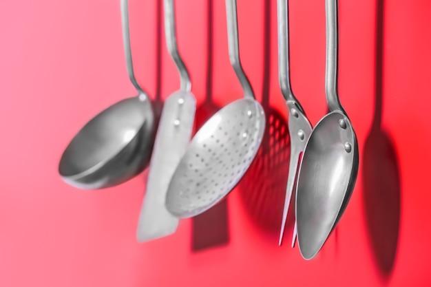 Set di utensili da cucina in metallo appesi al muro