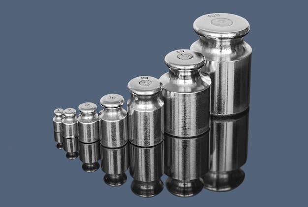 Set di pesi in metallo per bilance da laboratorio su uno sfondo scuro