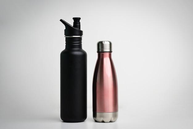 Set di moderne bottiglie thermos in diversi colori su sfondo bianco closeup di bottiglie di acciaio termo eco riutilizzabili per qualsiasi liquido
