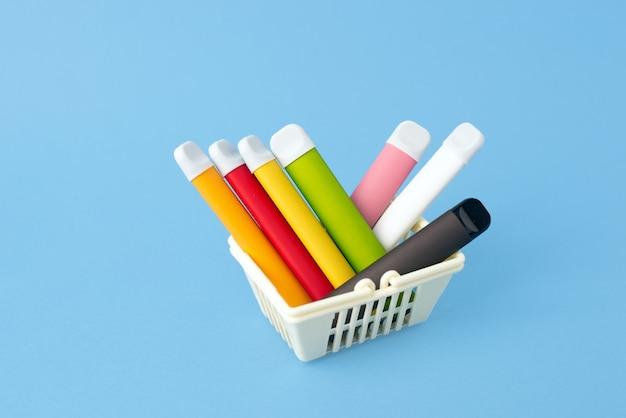 Una serie di bastoncini multicolori - dispositivi di svapo usa e getta, sigarette elettroniche in un cestino della spesa su una superficie blu.
