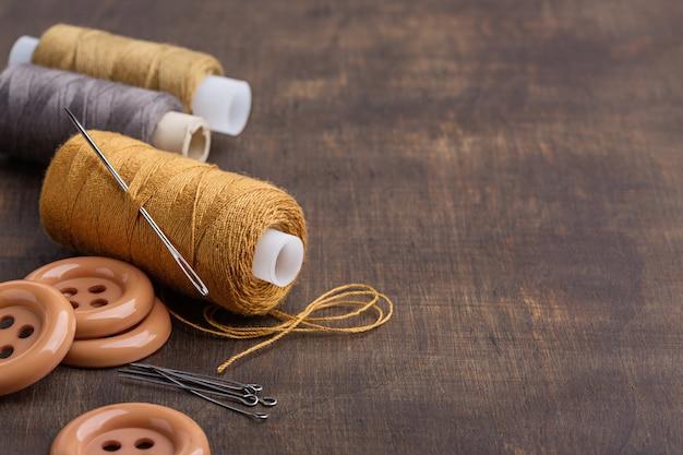 Set di fili multicolori su bobine, ago grande per cucire, bottoni e spille.