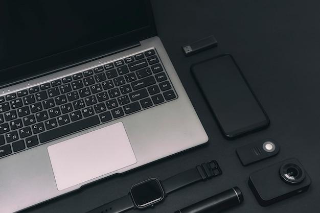 Set di dispositivi multimediali. laptop con una action cam, uno smartphone, uno smartwatch e un power bank con chiavetta usb su sfondo nero.