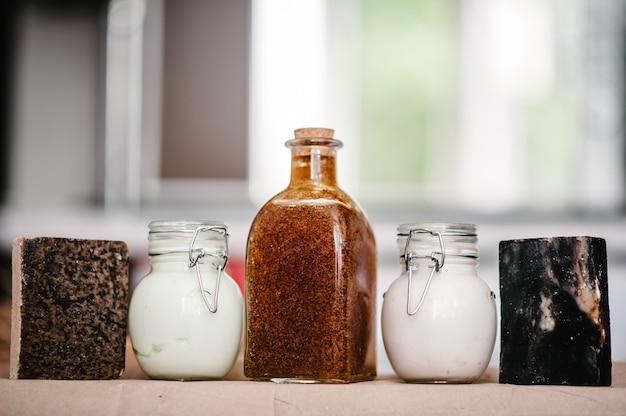 Una serie di cosmetici naturali per la cura del corpo su mensola di sapone, crema, shampoo in vaso, balsamo, gel doccia, scrub, lozione isolata.