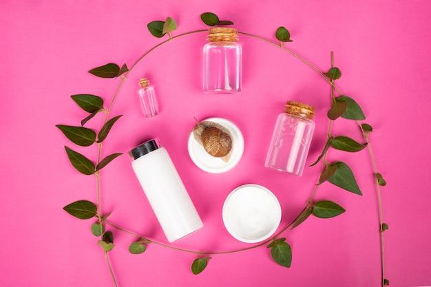 Set di cosmetici naturali da mucina di lumaca, kit per la cura della pelle su sfondo rosa.