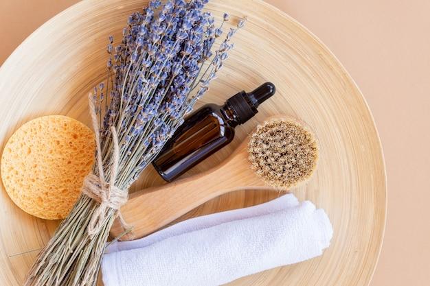 Set di cosmetici biologici naturali con olio essenziale di lavanda e accessori da bagno su un piatto di bambù. consumo sostenibile