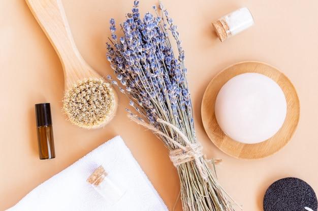 Set di cosmetici biologici naturali con olio essenziale di lavanda e accessori da bagno su fondo beige. consumo sostenibile.