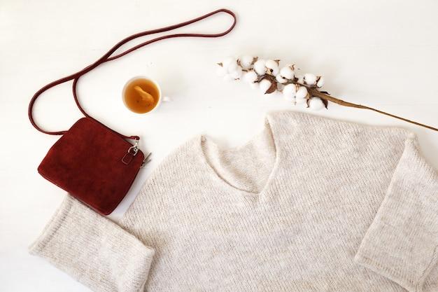 Un insieme di vestiti e scarpe delle donne alla moda ben disposti su una vista superiore del fondo bianco