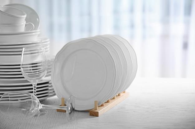 Set di nuovi piatti bianchi sul tavolo di legno, al chiuso