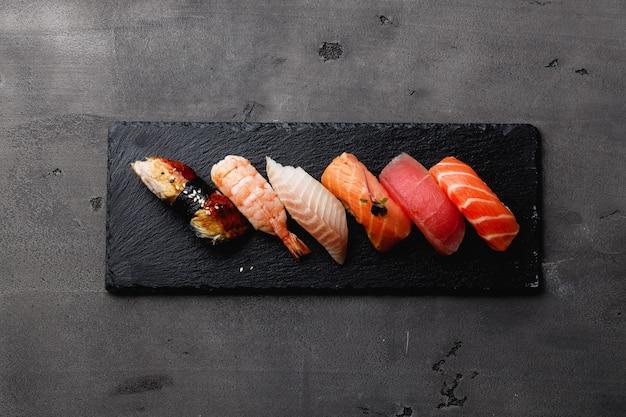 Set di nigiri sushi servito sulla piastra su sfondo grigio scuro