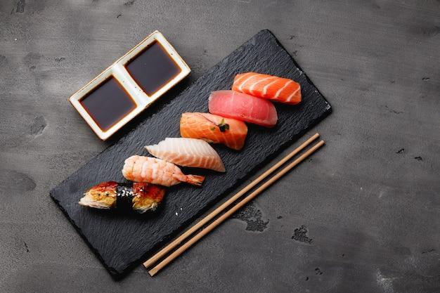 Set di nigiri sushi servito sul piatto sul tavolo grigio