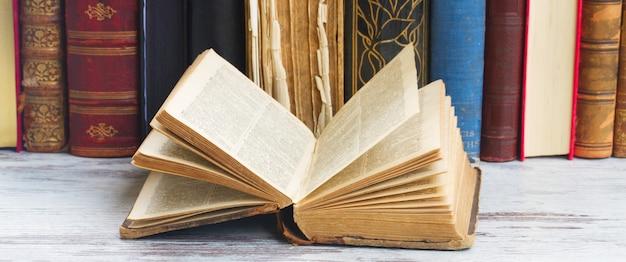 Insieme di vecchi libri con uno aperto sul desktop in legno bianco