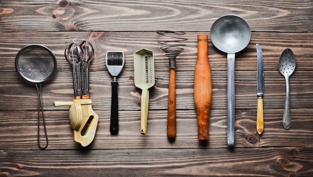 Un insieme di vecchi utensili da cucina e posate su un tavolo di legno. cucina vintage in cucina. vista dall'alto.