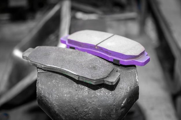 Set di pastiglie dei freni di automobili vecchie e nuove su un garage.