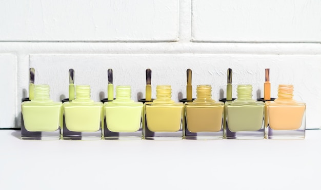 Set di bottiglie di smalto per unghie tinta verde aperta con spazzole. gruppo di smalto per unghie sul fondo bianco della parete. copia spazio.