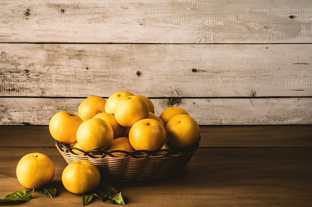 Set di arance all'interno del cesto intrecciato sulla parte superiore del tavolo in legno