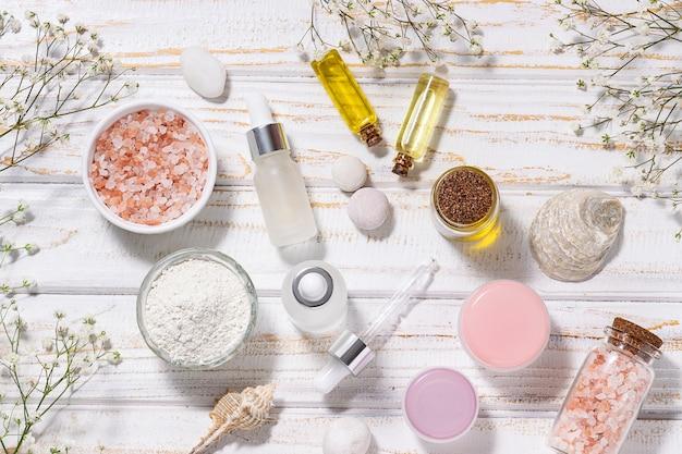 Set di cosmetici biologici per la cura della pelle e bellissimi fiori su sfondo bianco rustico vista dall'alto spa e concetto di benessere