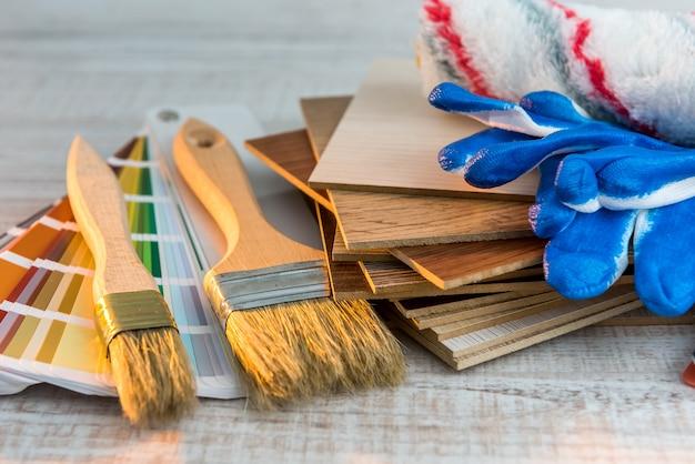 Set di pennelli e rullo sulla scrivania in legno. tutto da riparare