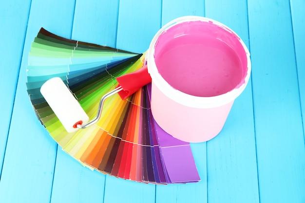 Set per la pittura: vaso di vernice, rullo di vernice sul tavolo di legno blu