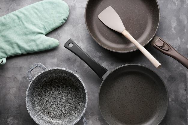 Set di padelle. vari utensili della cucina sulla tavola grigia, primo piano.