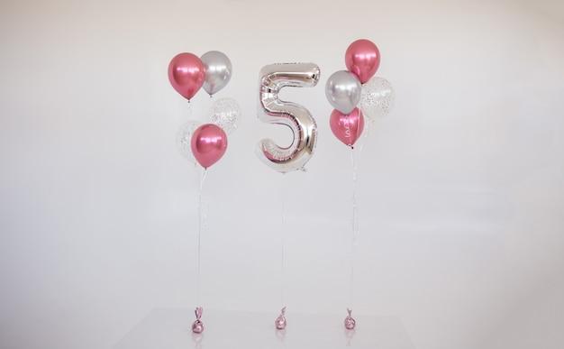 Una serie di palloncini rosa con elio e un numero gonfiabile cinque su uno sfondo bianco con un posto per il testo