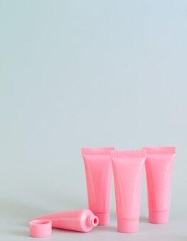 Set di tubi cosmetici rosa sul primo piano sfondo grigio. contenitori per prodotti termali per il tuo design. copia spazio
