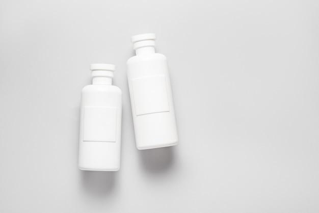 Set di shampoo in plastica, bottiglie di cosmetici su sfondo grigio