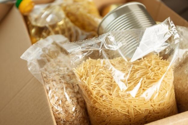 Una serie di prodotti in una scatola: pasta, burro, farina d'avena, cereali, cibo in scatola, pasta, riso. donazione per le persone rimaste senza soldi e senza lavoro durante l'epidemia di covid-19