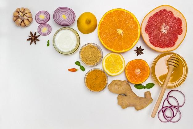 Set di prodotti di agrumi, zenzero, miele, aglio, cipolla, yogurt per una protezione naturale contro il virus. nutrizione medica a casa. lay piatto. copia spazio