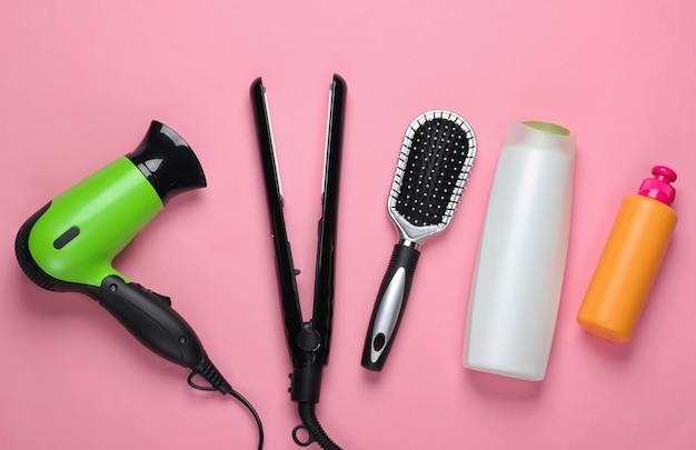 Set di prodotti e dispositivi per la cura dei capelli su pastello rosa