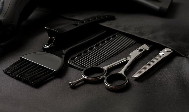 Set di strumenti da barbiere professionale nella tasca grembiule da stilista nero orizzontale senza persone