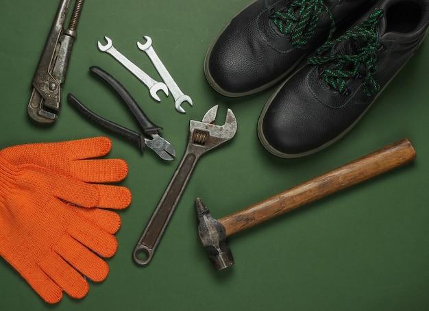 Set di strumenti di lavoro professionali e stivali su sfondo verde. vista dall'alto.