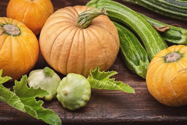 Insieme delle verdure della famiglia della zucca sulla vecchia superficie di legno scura. zucca, zucca, zucchine.