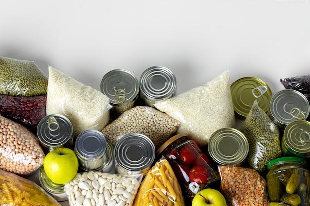 Set di cereali crudi, cereali, pasta e cibo in scatola sul tavolo.