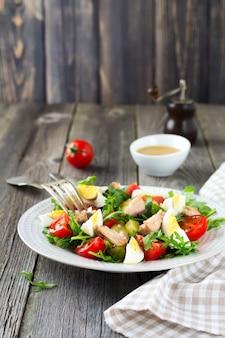 Set di ingredienti crudi patate, uova, rucola fresca, olio d'oliva, pepe, tonno in scatola, pomodorini, sale per preparare un'insalata nizzarda sulla vecchia superficie di legno