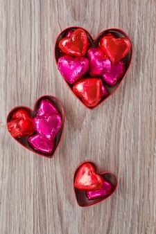 Set di caramelle cuore rosso e rosa sulla tavola di legno