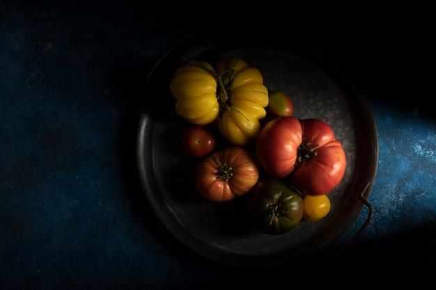 Insieme dei pomodori maturi nel vassoio, fondo di legno blu