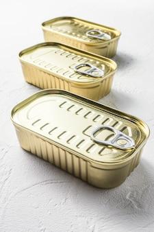 Set di stesse dimensioni da vicino cibo in scatola chiuso senza etichette, pesce, frutta, verdura, carne, zuppa diversi tipi di forme vista dall'alto su bianco