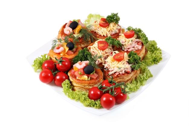 Impostare i panini sul piatto bianco con prosciutto e formaggio, gamberetti e salmone, immagine isolata su uno sfondo bianco. Foto Premium